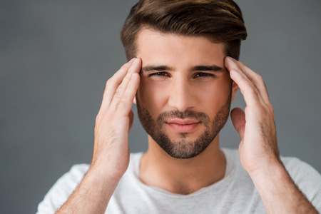 expressing negativity: Feeling headache. Depressed young man touching his head and expressing negativity while standing against grey background Stock Photo