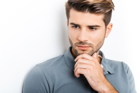 one man: Thoughtful handsome. Thoughtful young man keeping arms crossed and looking away while leaning at the wall