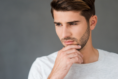 Waiting for inspiration. Thoughtful young man holding hand on chin and looking away while leaning at the wall Stock Photo