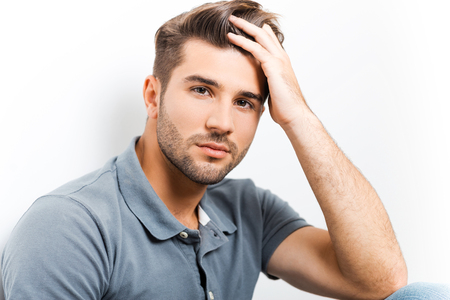 heartbreaker: Handsome heartbreaker. Handsome young man holding hand in hair and looking at camera Stock Photo