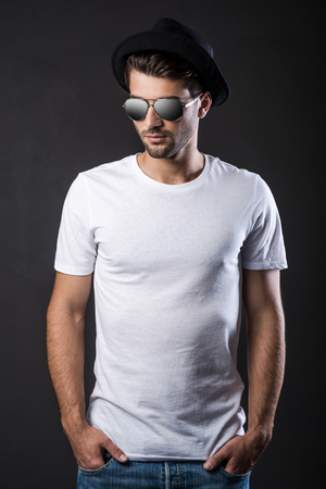 fedora hat: Cool and trendy. Handsome young man in sunglasses and fedora keeping hands in pockets while standing against black background
