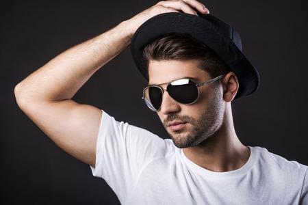hombre con sombrero: Confiados en su estilo perfecto. Hombre joven hermoso que ajusta su sombrero y mirando a otro lado mientras está de pie contra el fondo negro