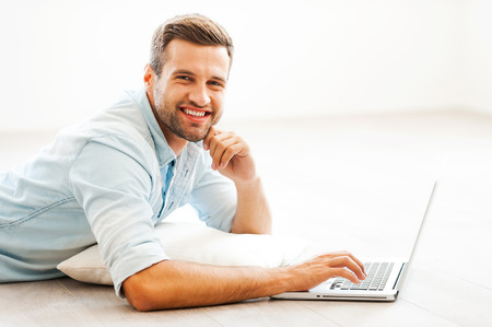 Spending time at home. Cheerful young man working on laptop and looking at camera while lying on the floor at his apartment Imagens
