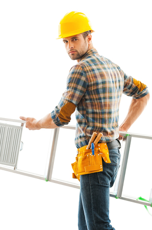 young worker: Handyman at work. Confident young repairman carrying ladder and looking at camera