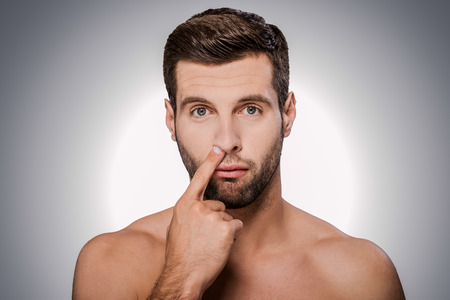 nose picking: Digging for gold. Portrait of handsome young shirtless man picking his nose while standing against grey background Stock Photo