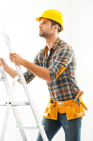 craftsperson: Climbing his way to the top. Confident young craftsperson climbing up the ladder and looking up