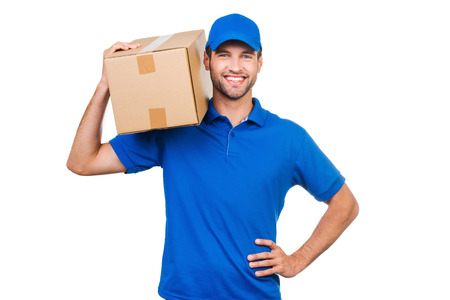 delivery package: Confident delivery man. Joyful young courier carrying cardboard box on shoulder and smiling while standing against white background