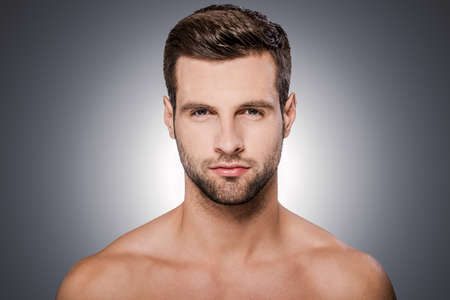 adult sex: Confident handsome. Portrait of handsome young shirtless man looking at camera while standing against grey background