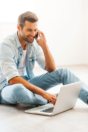 only one man: Doing business at home. Smiling young man working on laptop and talking on the mobile phone while sitting on the floor at his apartment Stock Photo