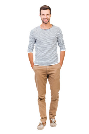 casual caucasian: Confident and stylish. Full length of cheerful young man holding hands in pockets and looking at camera while standing against white background
