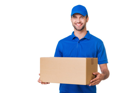 Cheerful delivery man. Happy young courier holding a cardboard box and smiling while standing against white background Foto de archivo