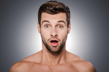 adult sex: Unbelievable! Portrait of surprised young shirtless man looking at camera and keeping mouth open while standing against grey background Stock Photo
