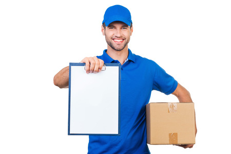 delivery box: Copy space on his clipboard. Cheerful young courier stretching out clipboard and smiling while standing against white background