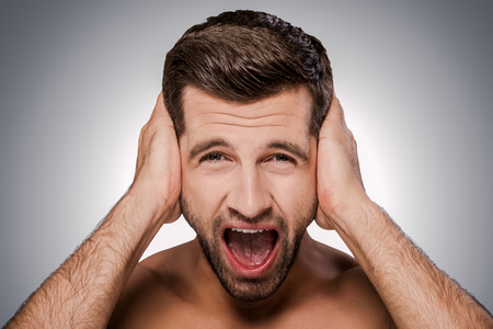 hands covering ears: Too loud sound. Portrait of frustrated young shirtless man shouting and covering ears by hands while standing against grey background Stock Photo