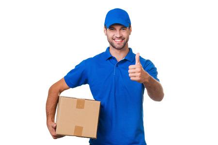 최고의 배달 서비스. 흰색 배경에 서있는 동안 쾌활 한 젊은 택배 판지 상자를 들고와 그의 엄지 손가락을 보여주는