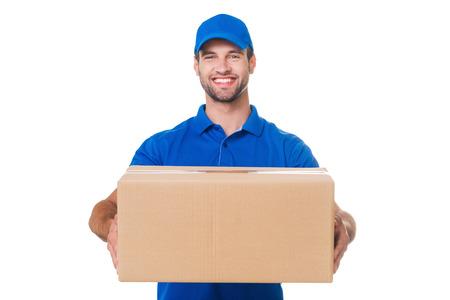 Neem uw pakket! Gelukkig jonge koerier die zich uitstrekt uit een kartonnen boxand glimlachen terwijl staande tegen een witte achtergrond Stockfoto