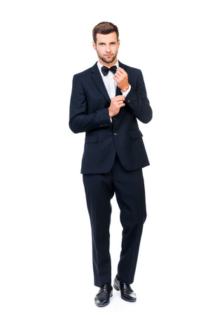 Charming handsome. Full length of handsome young man in full suit and bow tie adjusting his sleeve and looking at camera while standing against white background Stock Photo