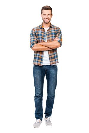handsome men: Guy affidabile. Tutta la lunghezza del giovane sorridente tenendo le braccia incrociate e guardando la fotocamera, mentre in piedi contro sfondo bianco