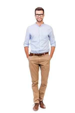confianza: Confiados en cualquier situaci�n. Hombre joven feliz con las manos en los bolsillos y mirando a la c�mara mientras est� de pie contra el fondo blanco Foto de archivo