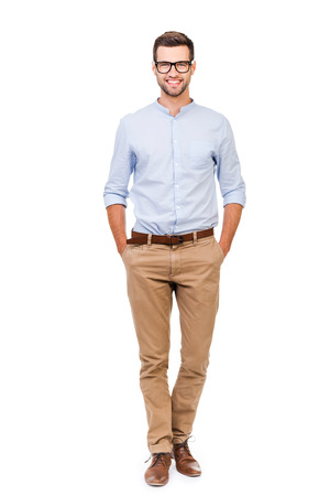 confidence: Confident in any situation. Happy young man holding hands in pockets and looking at camera while standing against white background
