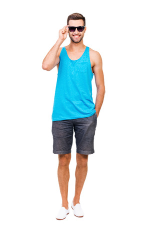 Ready for summer vacation. Full length of cheerful young man adjusting eyewear and looking at camera while standing against white background Stock Photo