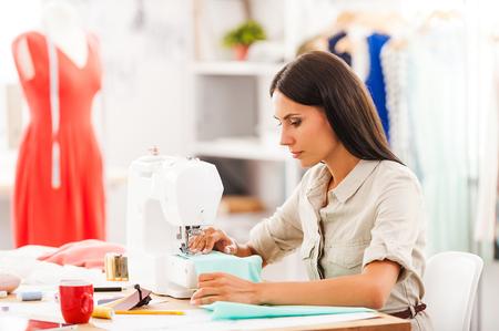 maquina de coser: Diseñador diligente. Vista lateral de la mujer joven de coser mientras estaba sentado en su lugar de trabajo en el taller de la moda