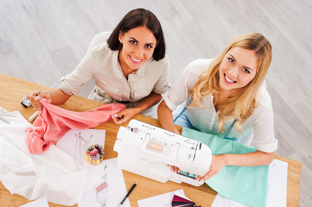 working place: Running their business together. Top view of two young women working together while sitting at their working place in fashion workshop