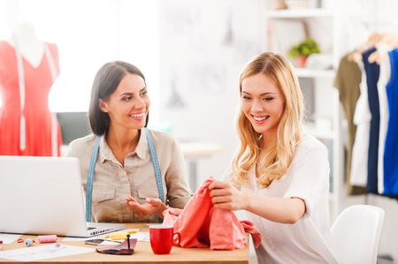 fashion style: What do you think about this color? Two smiling young women working together while sitting at the desk in their fashion workshop Stock Photo