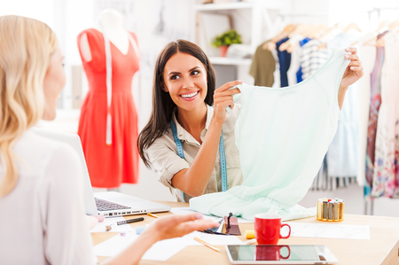 woman clothes: This dress is just perfect! Smiling young woman showing dress to another woman and smiling while both sitting at the table in fashion workshop Stock Photo