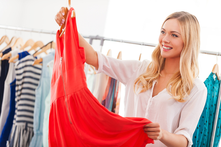 apparel: I like this dress! Smiling young woman holding dress and smiling while standing in clothing store