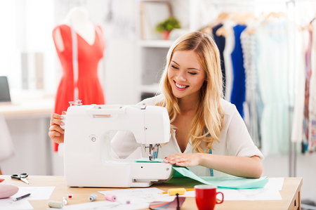 Creating new fashionable styles. Cheerful young woman sewing while sitting at her working place in fashion workshop