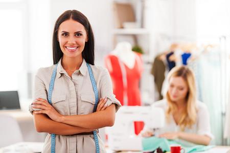 maquina de coser: Experto en moda confiado. Mujer joven alegre que mantener los brazos cruzados y sonriendo mientras que otra mujer de coser en el fondo
