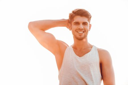 only the biceps: Fit and confident. Low angle view of young muscular man posing and looking at camera while standing against sky