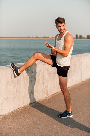 warming up: Warming up before jogging. Handsome young muscular man warming up before running while standing outdoors
