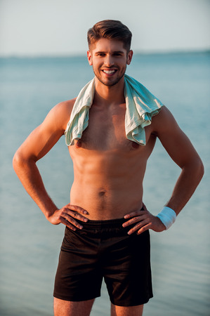 young guy: Fitness and fresh air. Smiling young muscular man holding hands on hips and looking at camera while standing at the seaside Stock Photo