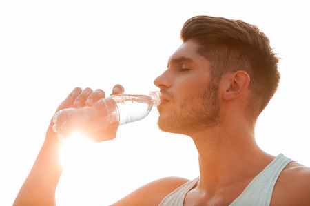 Staying hydrated. Low angle view of young man drinking water and keeping eyes closed while standing outdoors