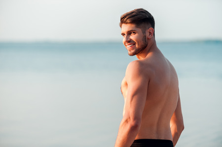 Strong and handsome. Rear view of young muscular man looking over shoulder and smiling while standing at the seaside