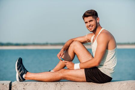 mp3 player: Enjoying his favorite music. Side view of cheerful young muscular man in headphones holding MP3 player and smiling while sitting on parapet
