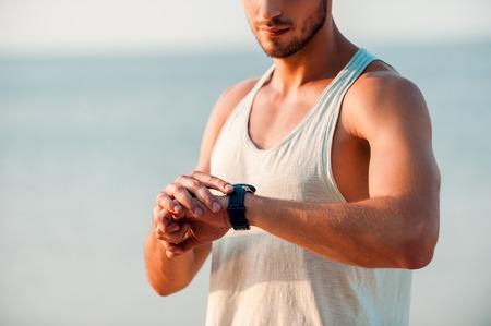 cheque en blanco: Fue un gran entrenamiento. Recorta la imagen de la joven hombre musculoso tiempo comprobando en sus relojes de pie al aire libre