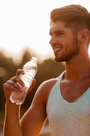 only one man: Water is a key to good workout. Handsome young muscular man holding a bottle and smiling while standing outdoors Stock Photo