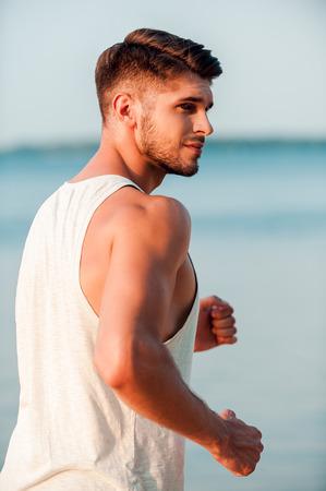 Mantener su cuerpo en gran forma. Vista lateral de hombre musculoso joven confía mirando a otro lado mientras se ejecuta a lo largo en la playa