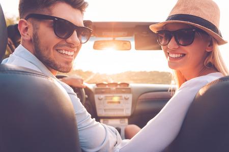 manejando: Nuestro viaje de fin de semana perfecto. Vista trasera de la pareja joven alegre mirando por encima del hombro y sonriendo mientras est� sentado en el interior de su convertible