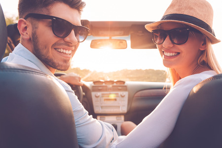 car side view: Our perfect weekend journey. Rear view of cheerful young couple looking over shoulder and smiling while sitting inside of their convertible
