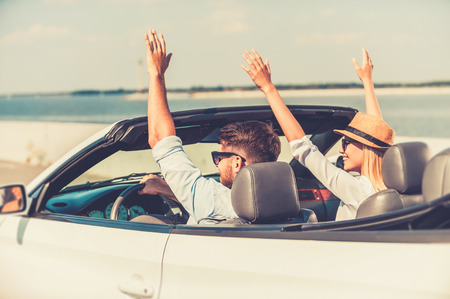 car on the road: Perfect start of their weekend. Excited young couple keeping arms raised while riding in their white convertible Stock Photo