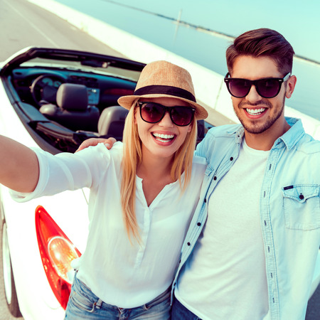 road of love: Capturing the bright moments. Top view of cheerful young couple making selfie while standing near their white convertible Stock Photo