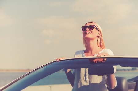freedom woman: Feeling freedom. Beautiful young woman in eyewear enjoying road trip while standing up in white convertible