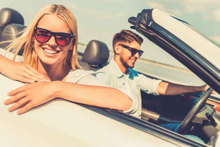 feeling happy: Feeling relaxed and free. Happy young woman leaning at the vehicle door and looking at camera while her boyfriend sitting near and driving convertible Stock Photo