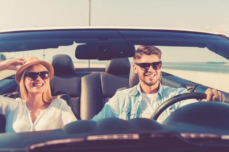 Deze weg is alleen voor ons! Blije jonge paar lachende tijdens het rijden in hun converteerbare Stockfoto