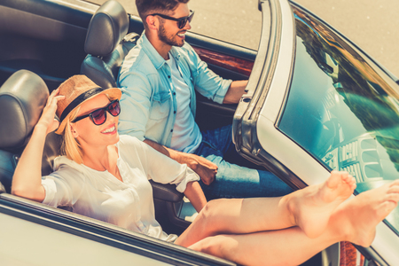 Weekend drive. Top view of smiling young woman relaxing while her boyfriend driving their convertible Stock Photo