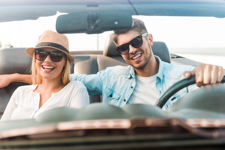 parejas: Feliz viajar juntos. Alegre joven pareja sonriendo mientras viajaba en su convertible Foto de archivo